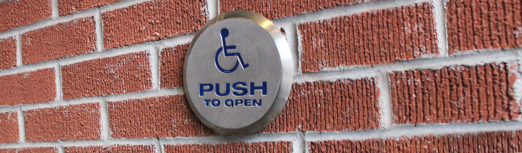 accessible door opener button on a brick wall