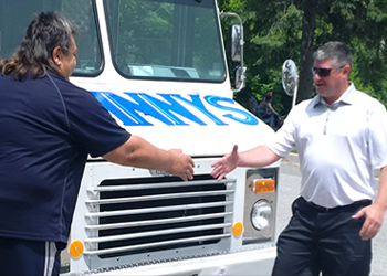Mayor Scott shaking another gentleman's hand in front of a truck outside