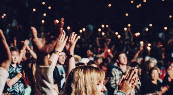 a crowd of people with hands in the air and clapping