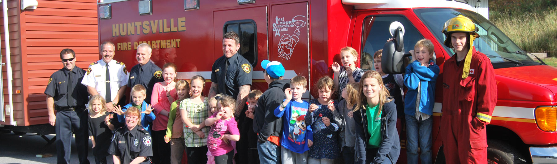 Kids posing with Fire fighters and the fire safety house