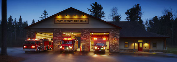 evening image of a firehall and trucks in bays