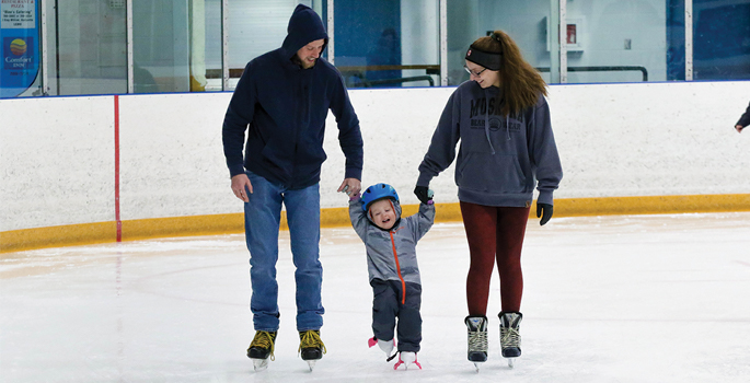 two adults and a child skating